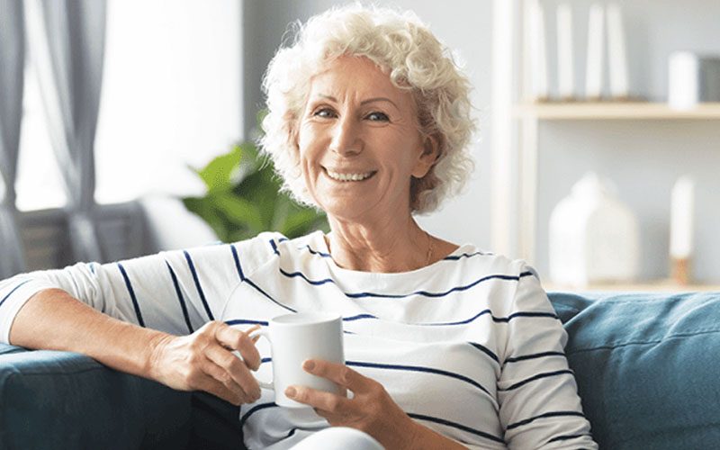 Older woman smiling on couch with coffee cup in hand
