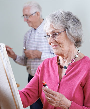 Older couple painting in an art class