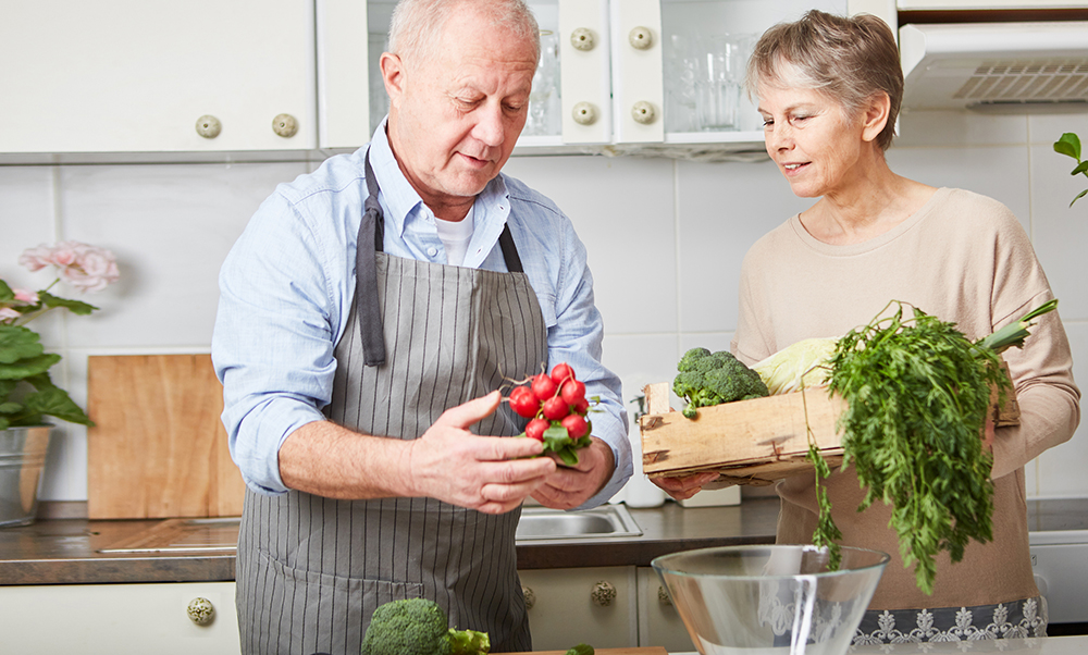 Older couple preparing vegetables in their kitchen